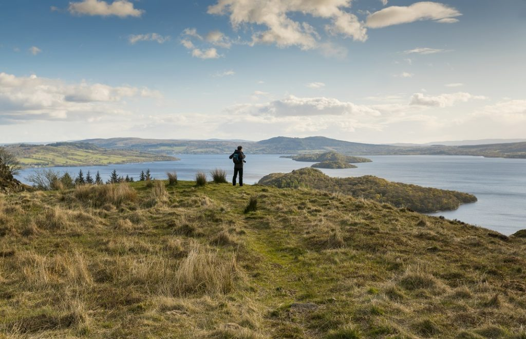Walker taking in the view of Loch Lomond from Conic Hill part of the West Highland Way